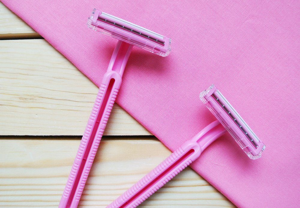 Two pink women's disposable razors on wooden table.