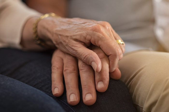 early-onset Alzheimer's   elderly couple holding hands comforting each other
