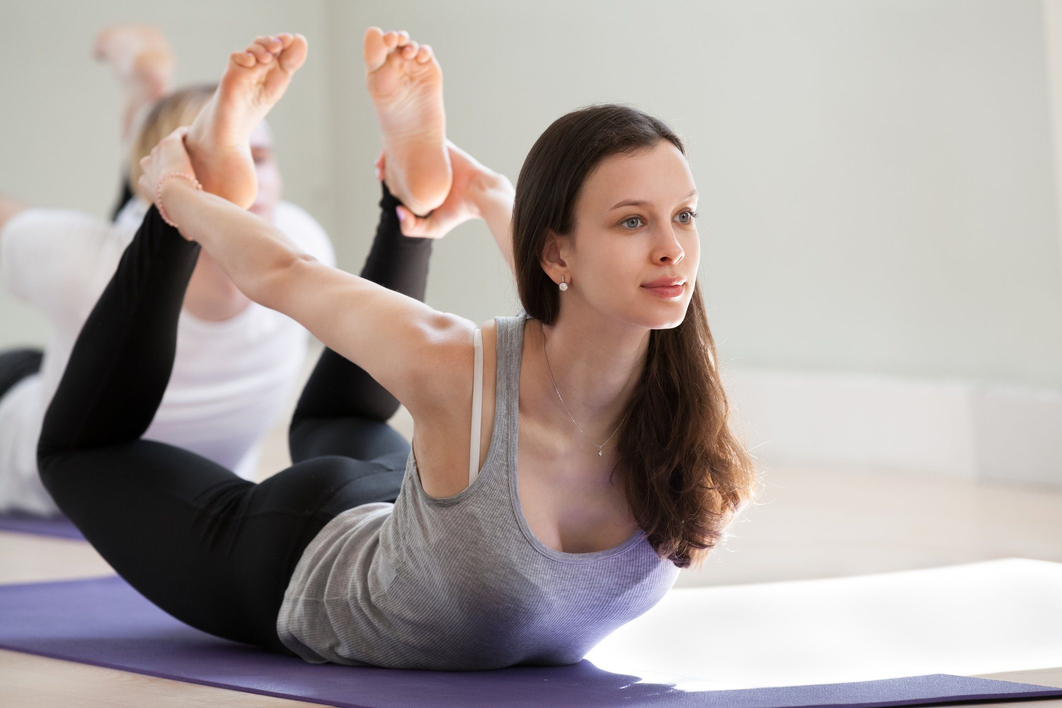 woman doing yoga bow pose