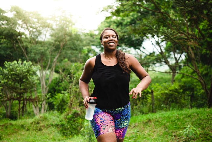 situations that cause dehydration | woman walking and exercising in nature