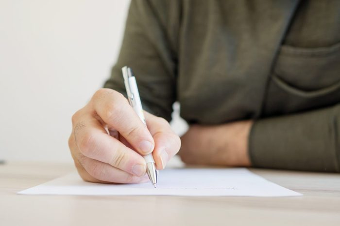 early-onset Alzheimer's   close up of man writing on paper