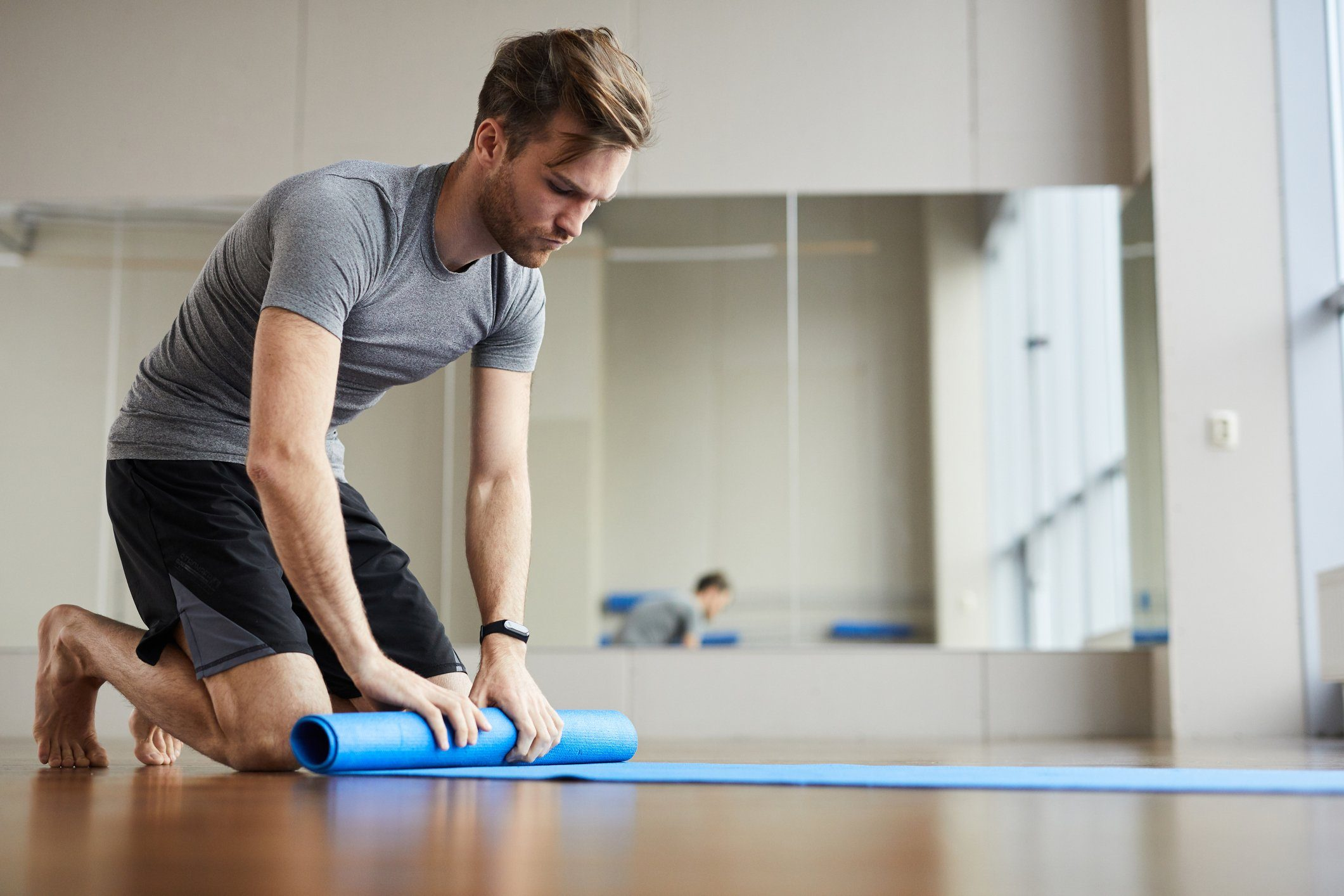 young man rolling out yoga mat in yoga studio