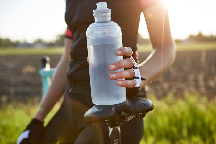 situations that cause dehydration | close up of cyclist holding water bottle