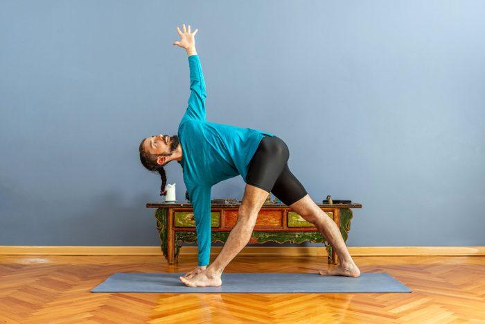 man doing revolved triangle yoga pose
