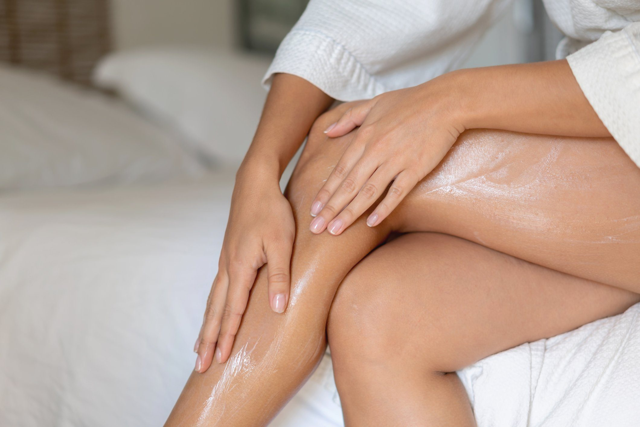 beauty products | applying body oil moisturizer to legs