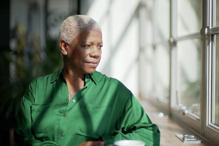 early-onset Alzheimer's   mature woman sitting at home looking out the window