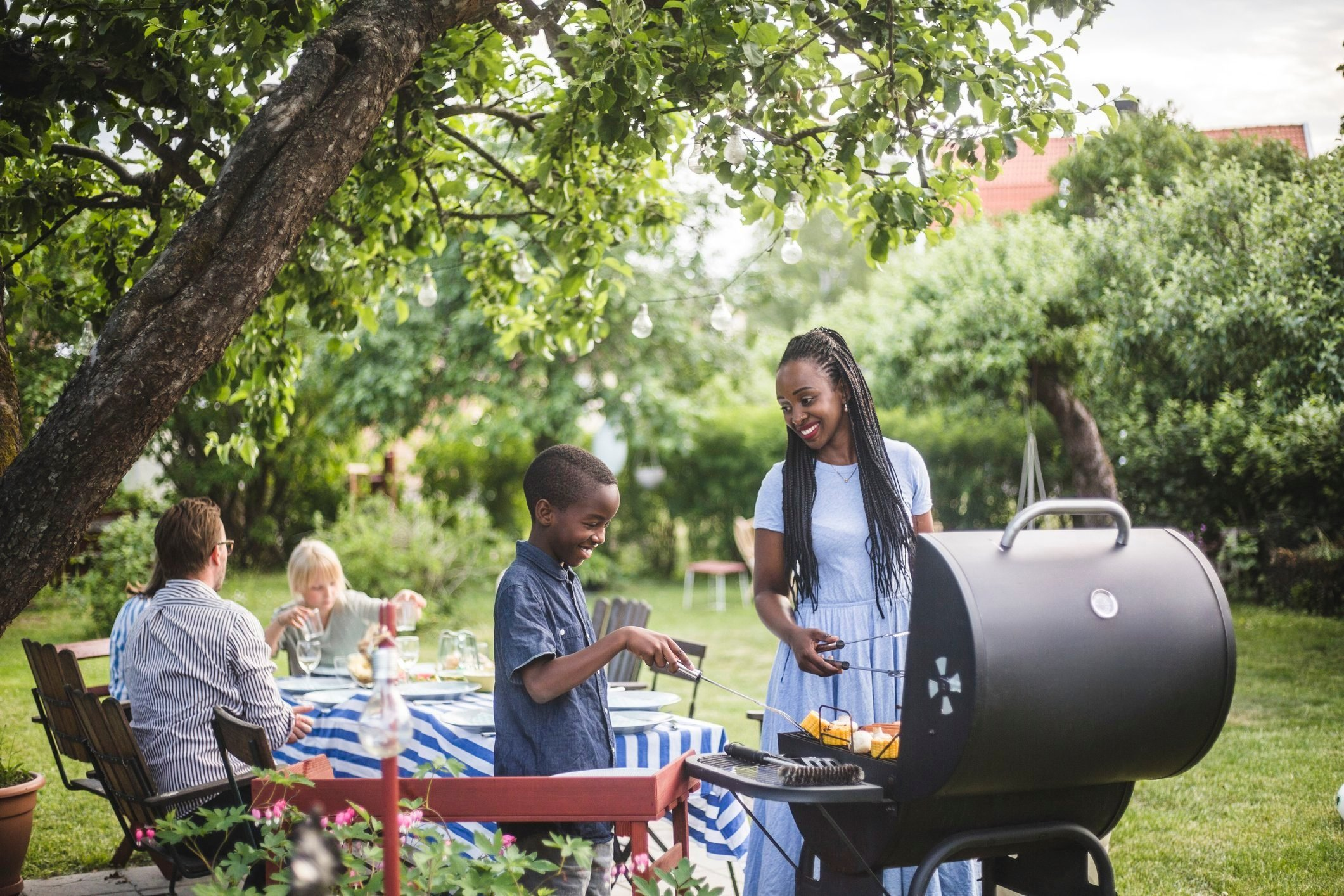 healthier grilling   mother and son grilling food for barbecue with family