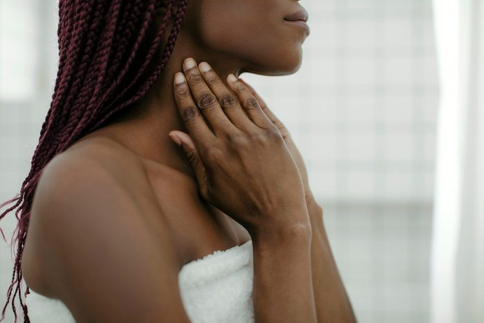 skin care practices for every age | woman applying lotion to neck