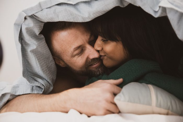 couple in bed under the covers