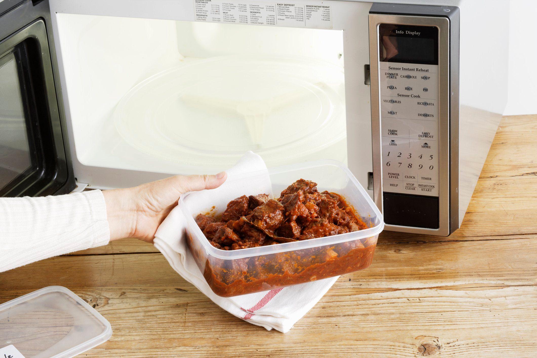 doctors eat for breakfast | woman heating leftovers in microwave