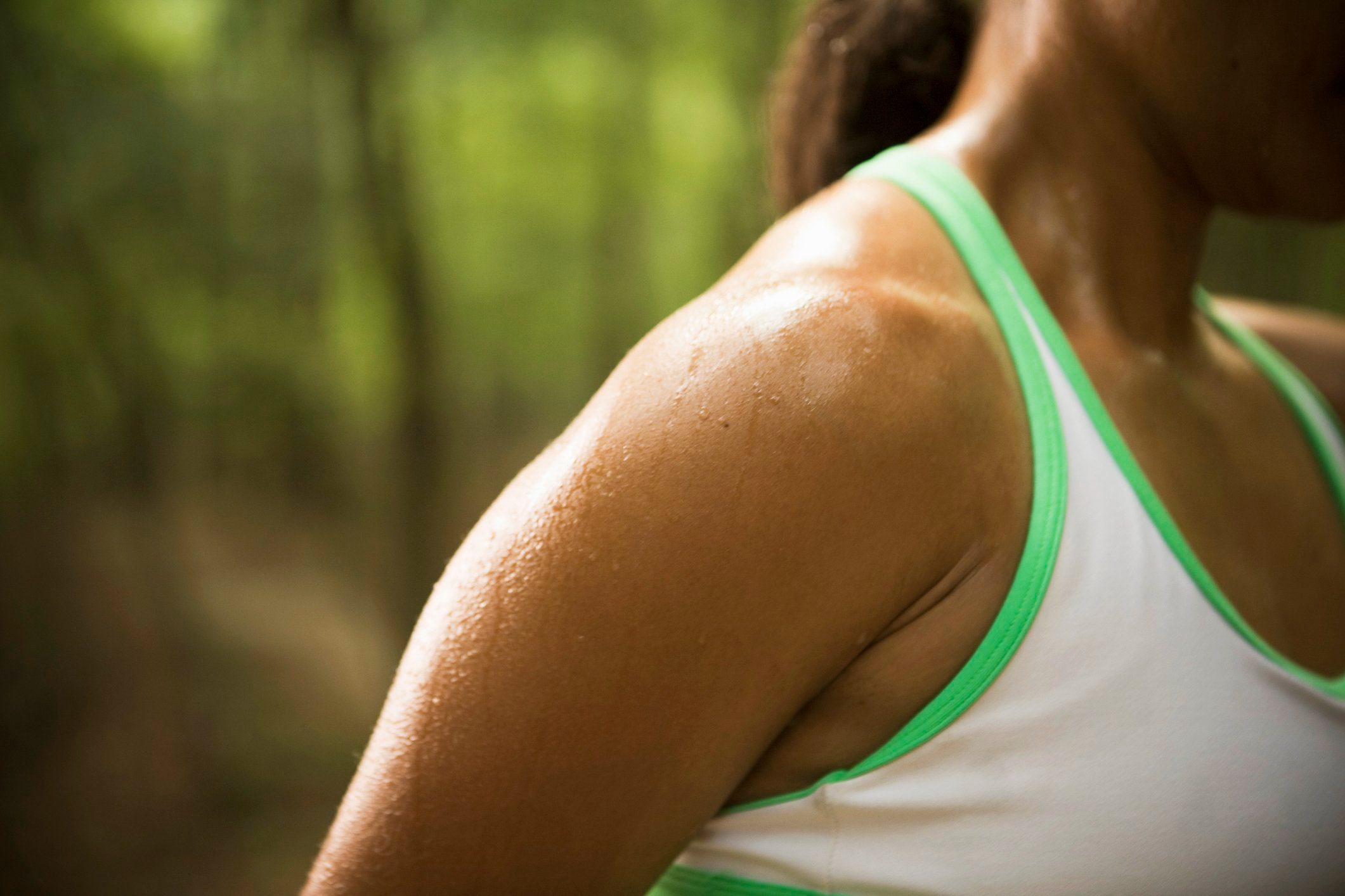 cause dehydration | close up of woman's sweaty shoulder outside during exercise