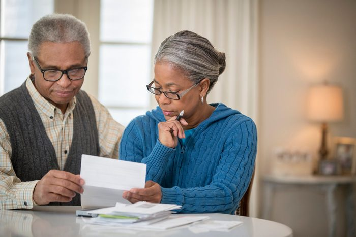 early-onset Alzheimer's   mature couple paying bills at home