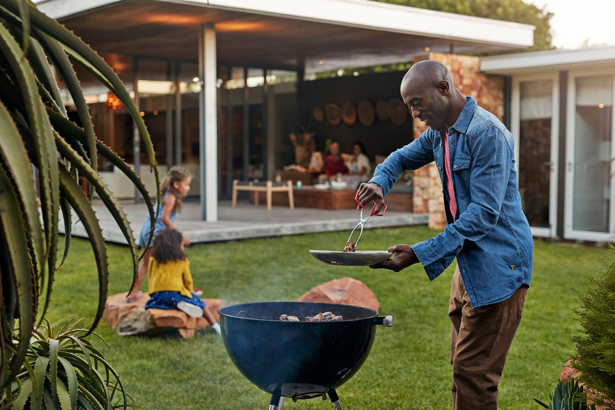 healthier grilling   man grilling in his backyard with family