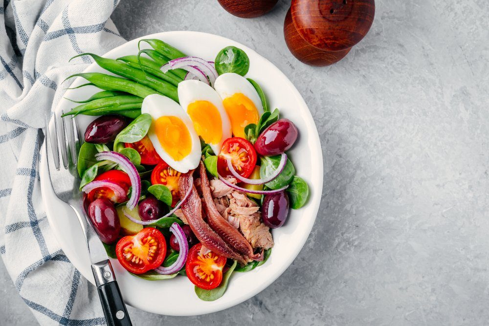 nicoise salad with tuna, anchovies, eggs, green beans, olives, tomatoes, red onions and salad leaves on gray background | foods to avoid before workout