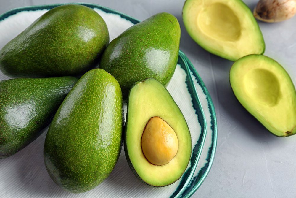 Plate with ripe avocados on grey table | foods to avoid before workout