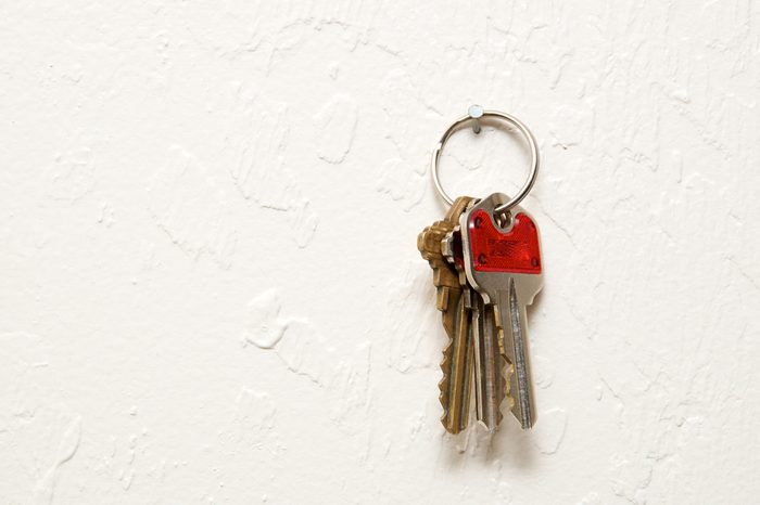 early-onset Alzheimer's   A keyring with three keys hanging on nail on wall.