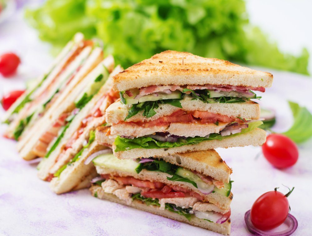 Club sandwich with chicken breast, bacon, tomato, cucumber and herbs | foods to avoid before workout