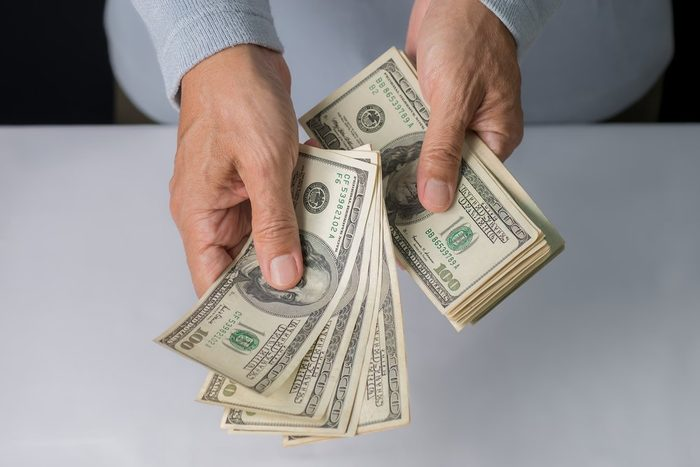 early-onset Alzheimer's   Man hand holding money,bribery concept. Business man giving stack of US dollar.