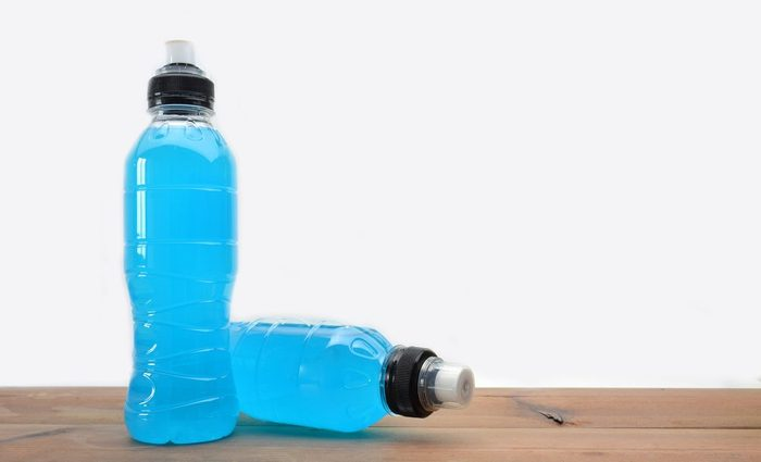 sports drink on wooden table and white background | foods to avoid before workout