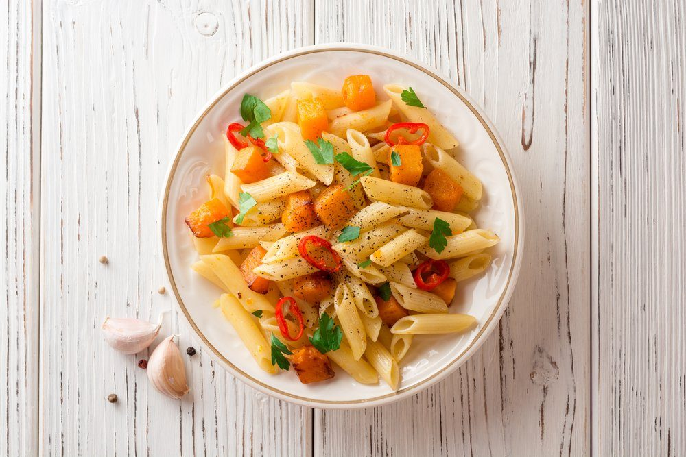 Penne pasta with pumpkin, chilli and parsley in plate on white wooden background | foods to avoid before workout