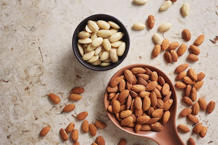 Peeled (blanched) and unblanched whole almonds. Shelled almonds on a spoon with a small black bowl of blanched almonds. | foods to avoid before workout