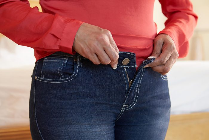 woman buttoning her jeans