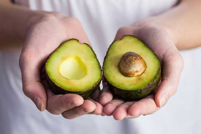 hands holding an avocado