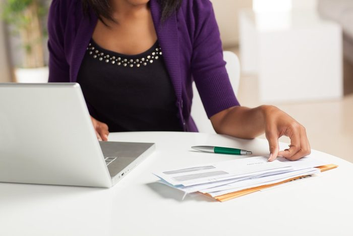 signs your body is in trouble | woman paying bills at laptop