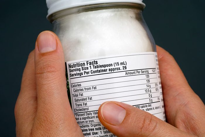 reach your goal weight   Reading a nutrition facts on organic coconut oil jar. Close-up.