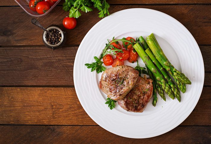 reach your goal weight   Barbecue grilled beef steak meat with asparagus and tomatoes. Top view