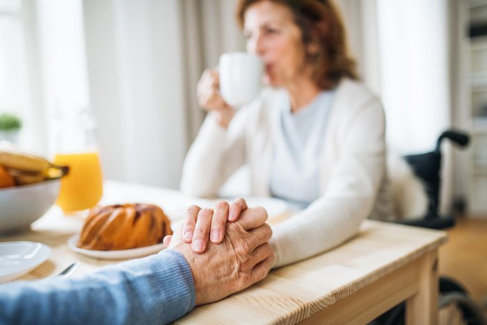 close up of couple holding hands at table
