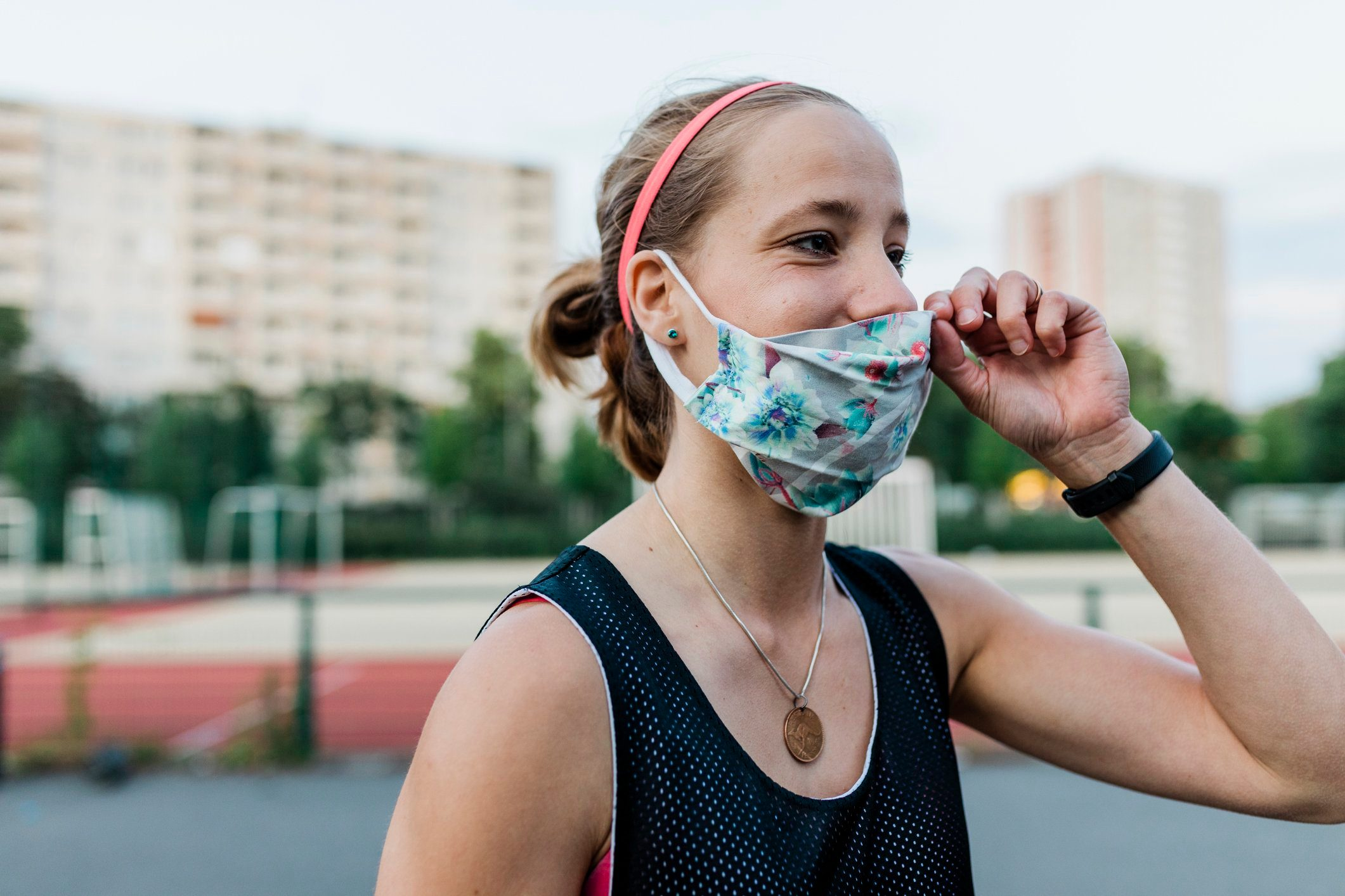 woman putting on face mask outside