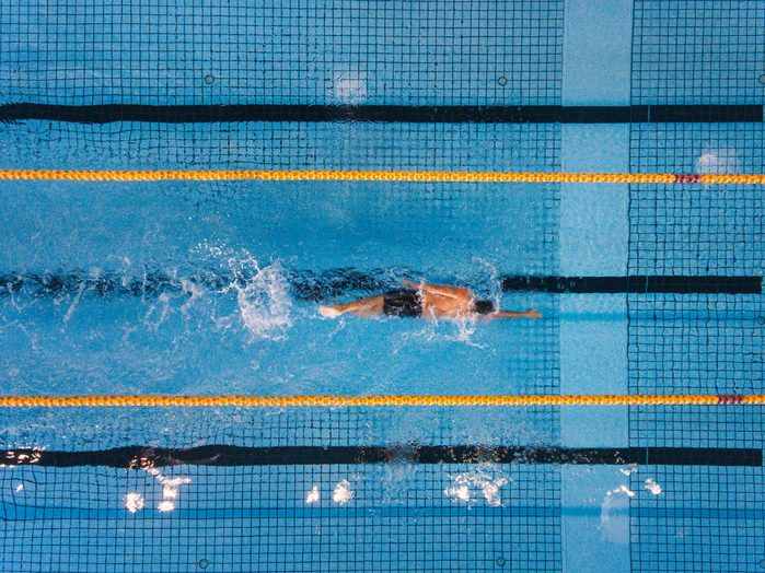 social distancing sports   overhead shot of man swimming laps in pool