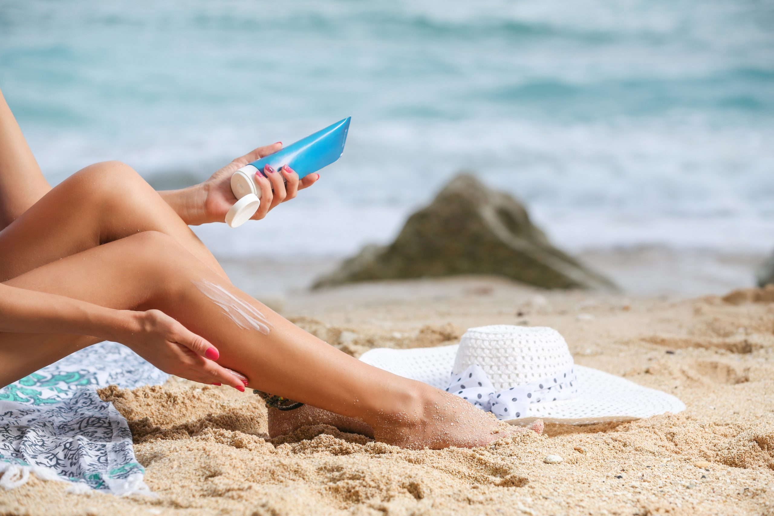 beauty products | Girl applying sunscreen on her legs