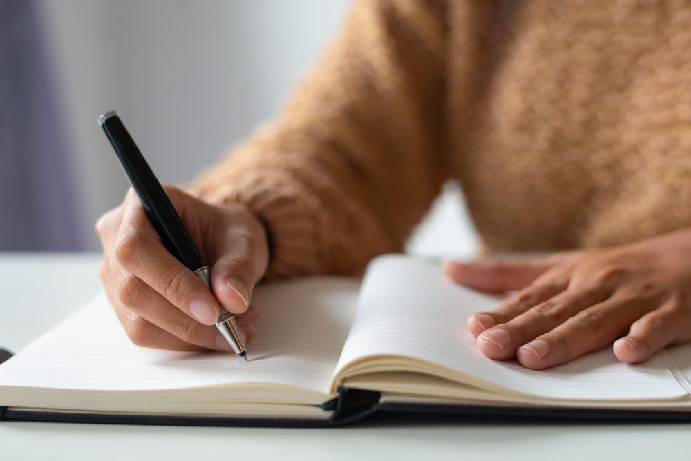 signs your body is in trouble | person writing in a journal