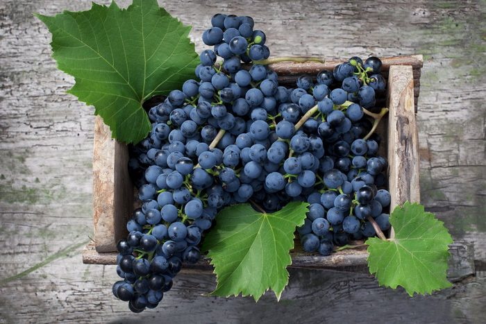 Big clusters of ripe blue grapes in a wooden box