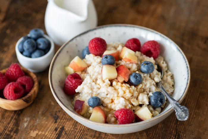 diabetic breakfast | Oatmeal porridge with berries and honey on wooden table