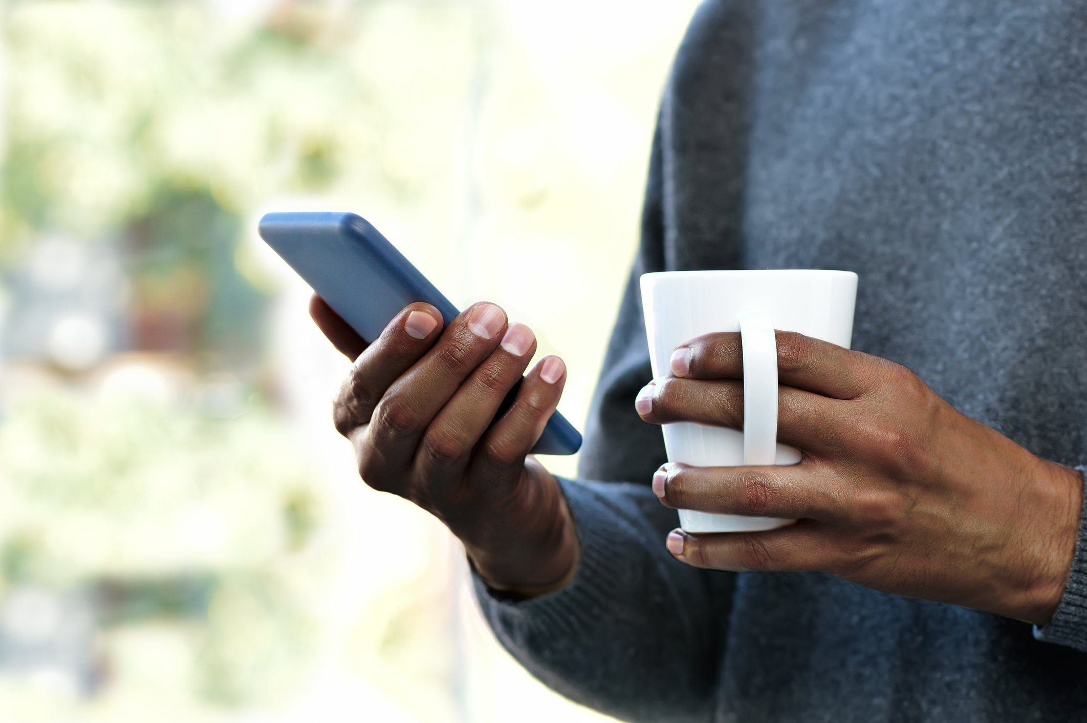 nomophobia | close up of person holding coffee mug and smartphone