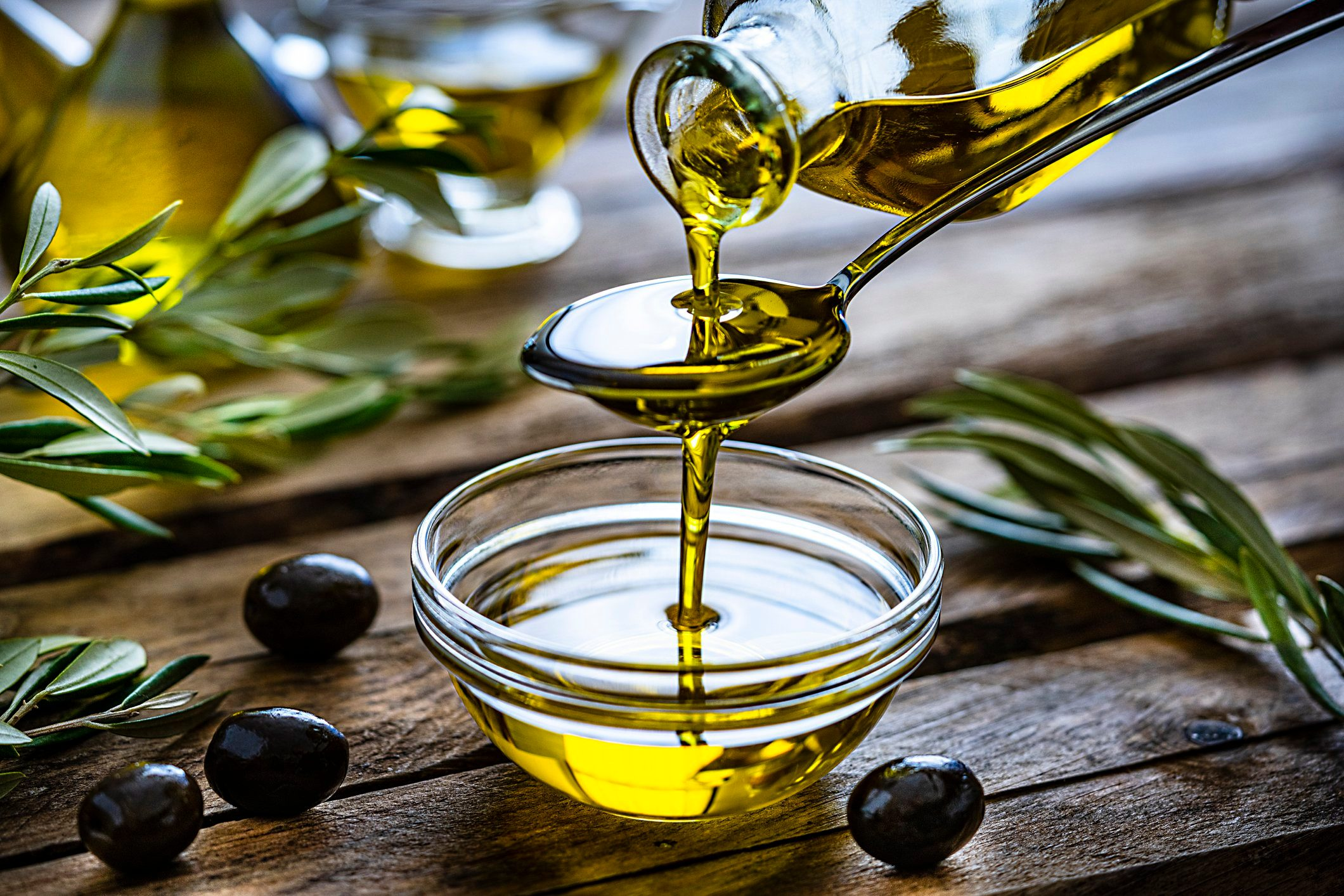 mediterranean diet | pouring extra virgin olive oil in a glass bowl