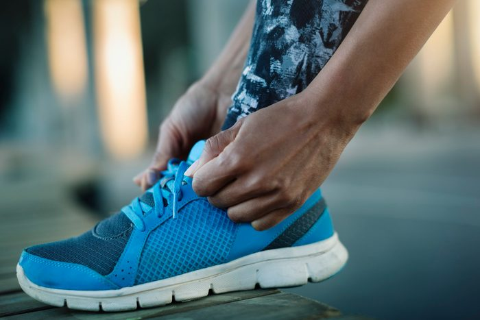 close up of woman tying sneakers before workout