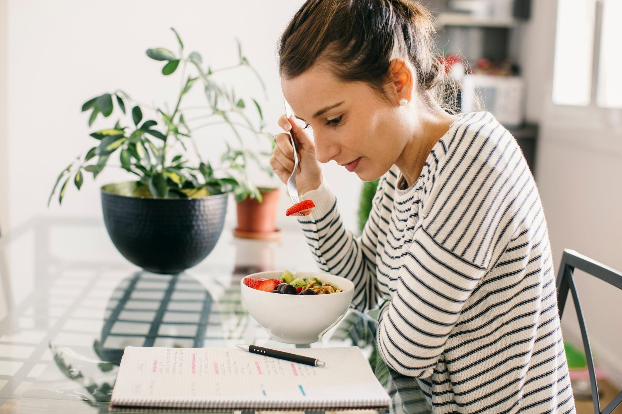 diabetic breakfast | Woman sitting at table with fruit muesli looking at notepad