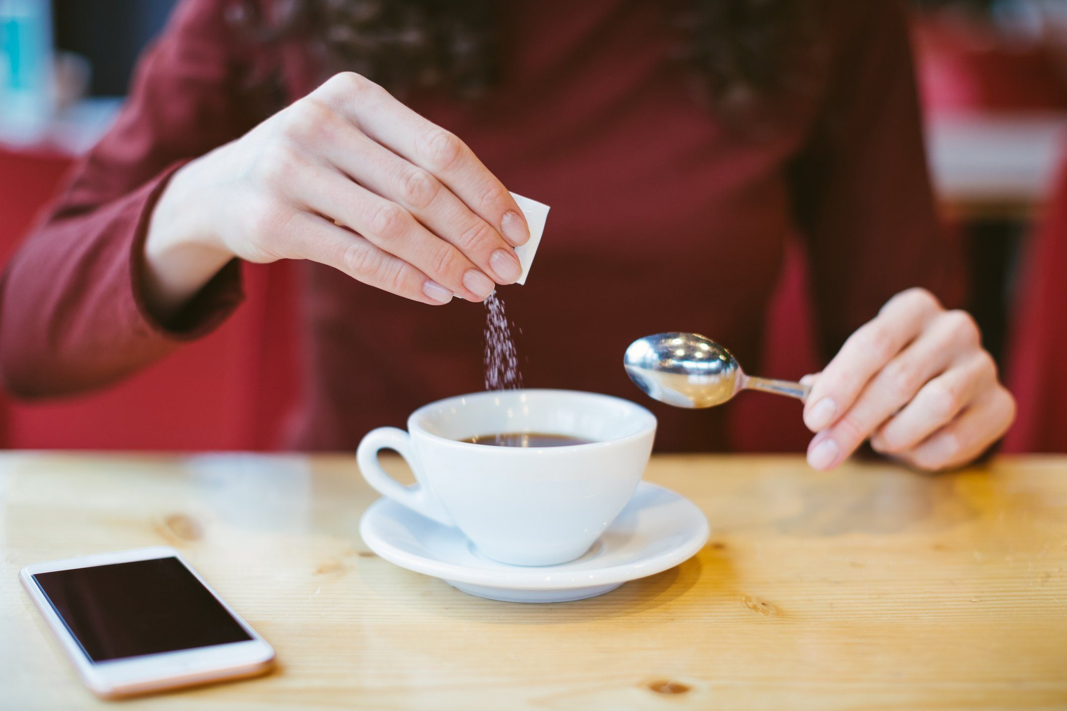 stevia bad for you | Woman's hands pouring sugar into black coffee - girl sitting at the table with espresso and smartphone - blood and glycemic index control for diabetes -excess of white sugar in food concept