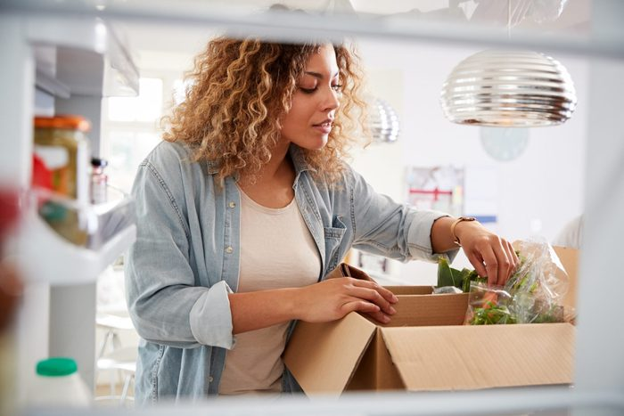 View Looking Out From Inside Of Refrigerator As Woman Unpacks Online Home Food Delivery