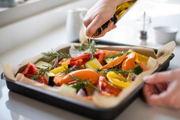 healthiest cooking oils   drizzling olive oil on pan of vegetables