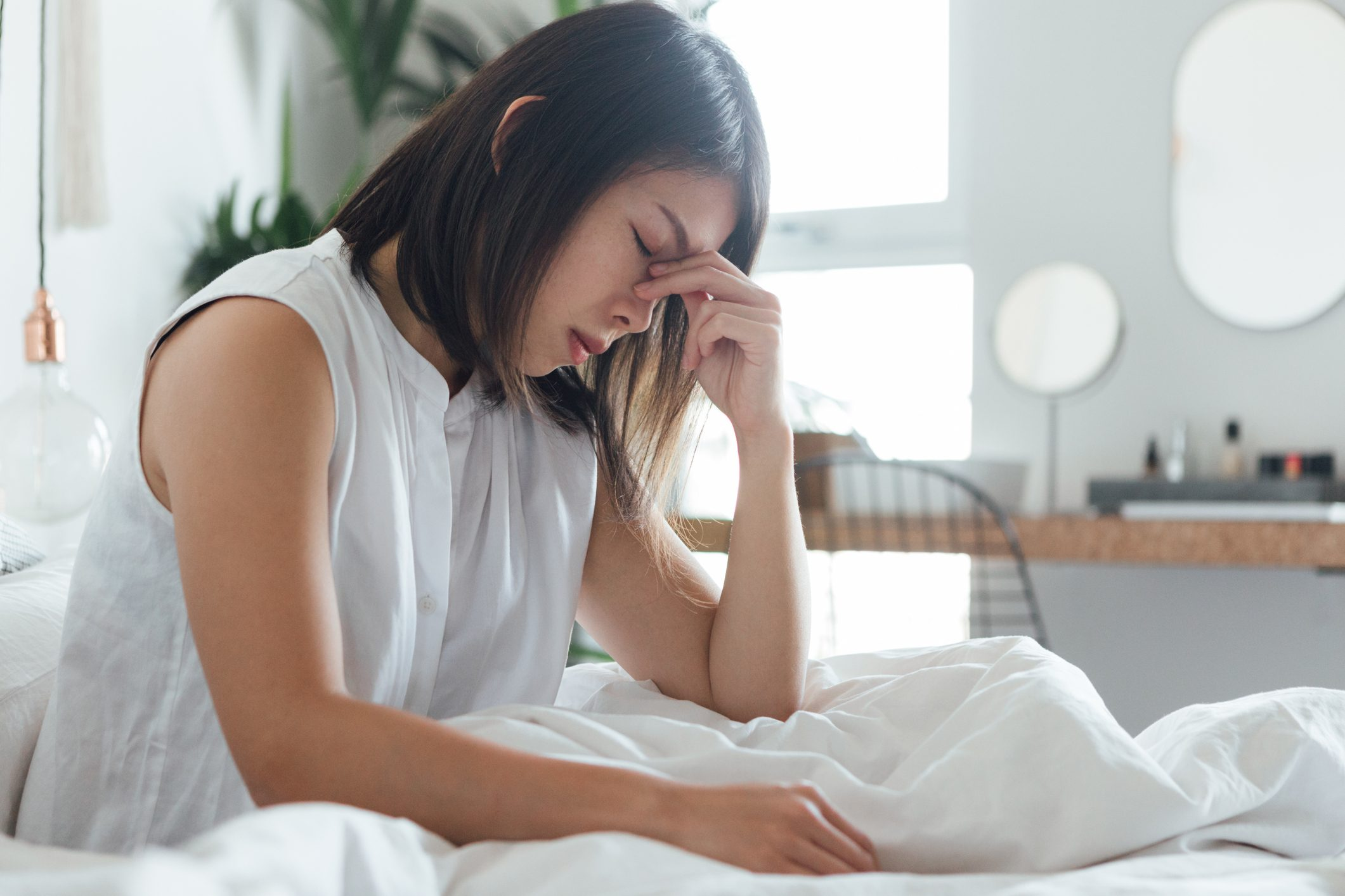 period flu | Young Woman Suffering Headache In Bed