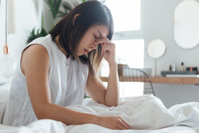 period flu | Young Woman Suffering Headache In Bed