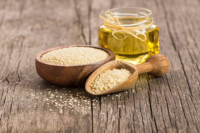 healthiest cooking oils   Glass bottle of sesame oil and raw sesame seeds