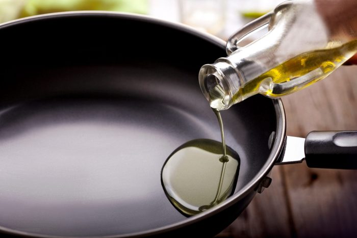 Pouring cooking oil in frying pan