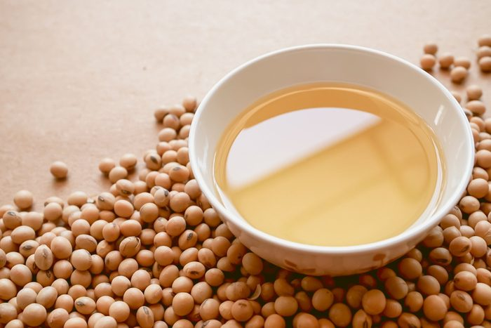 healthiest cooking oils   oil and soybeans on brown paper