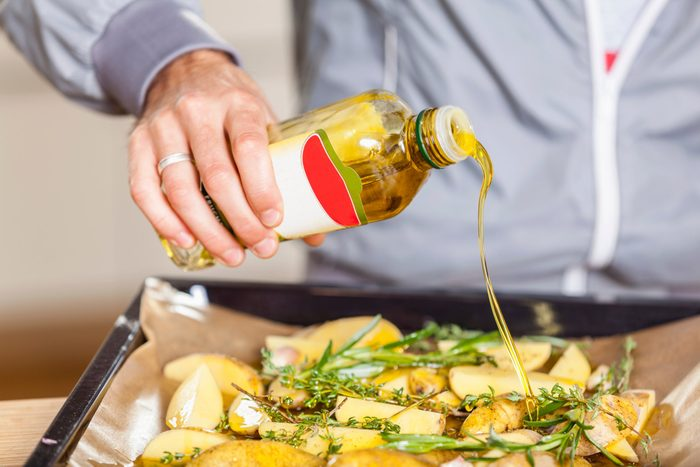healthiest cooking oils   Pouring oil over potato wedges on baking tray